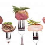 Wildfleisch, Rinderroulade, Lammrücken, Hühnerbrust und Rinderfilet auf einer Gabel